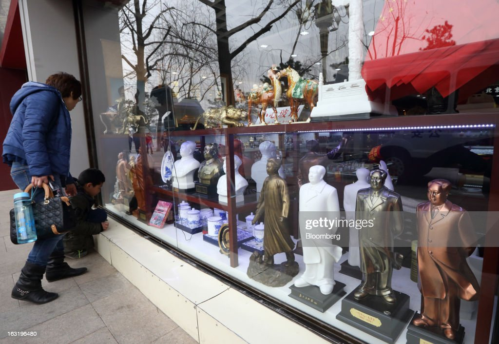 A woman and child look at statues of former Chinese leader Mao Zedong outside a store in Beijing, China, on Wednesday, March 6, 2013. China maintained its economic-growth target at 7.5 percent for 2013 while setting a lower inflation goal of 3.5 percent, setting up a challenge for new leaders to keep prices in check without harming expansion. Photographer: Tomohiro Ohsumi/Bloomberg via Getty Images