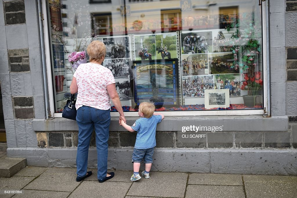 A woman and child look in at the window of a shop displaying images of local heritage in the border town of Selkirk in Scotland close to the border between England and Scotland on June 26, 2016. Scotland's First Minister Nicola Sturgeon campaigned strongly for Britain to remain in the EU, but the vote to leave has given the Scottish National Party leader a fresh shot at securing independence. Sturgeon predicted more than a year ago that a British vote to leave the alliance would give pro-European Scots cause to hold a second referendum on breaking with the UK. SCARFF