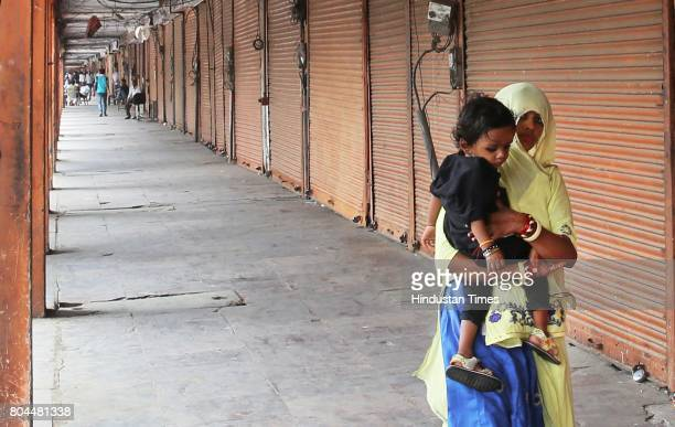 A woman and child pass shuttered shops during the nationwide shutdown to protest GST on June 30 2017 in Jaipur India The traders said they were not...