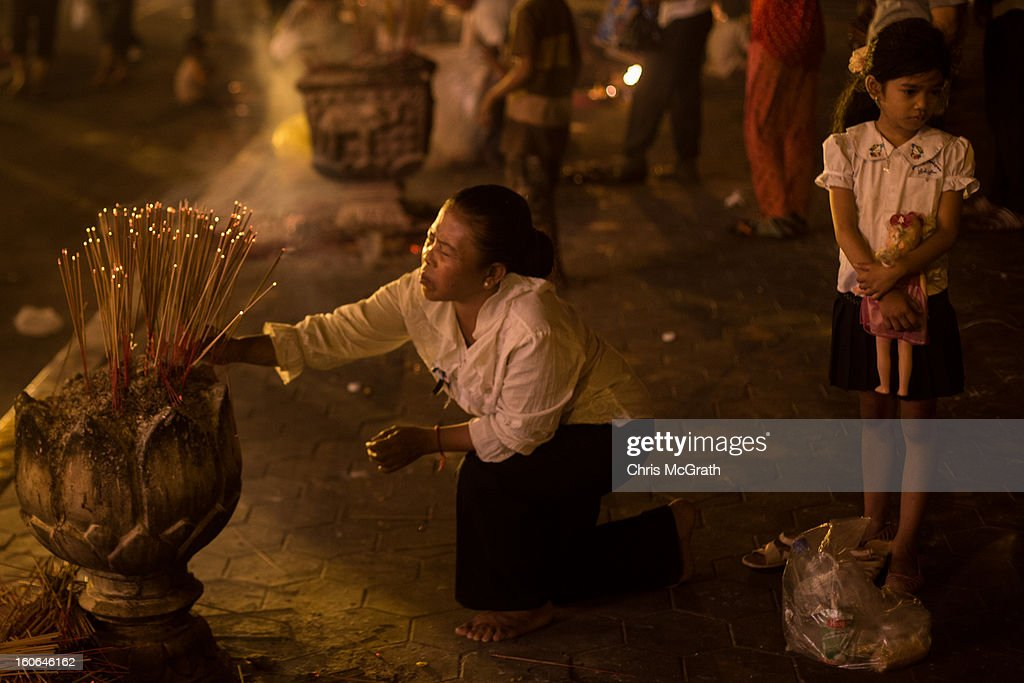 A woman and child place incense sticks outside the Royal Palace after the cremation ceremony for former King Norodom Sihanouk on February 4 2013 in...