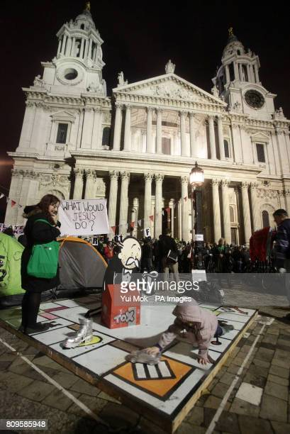 A woman and child play on a giant Monopoly board at the Occupy London Stock Exchange demonstration outside St Paul's Cathedral in London