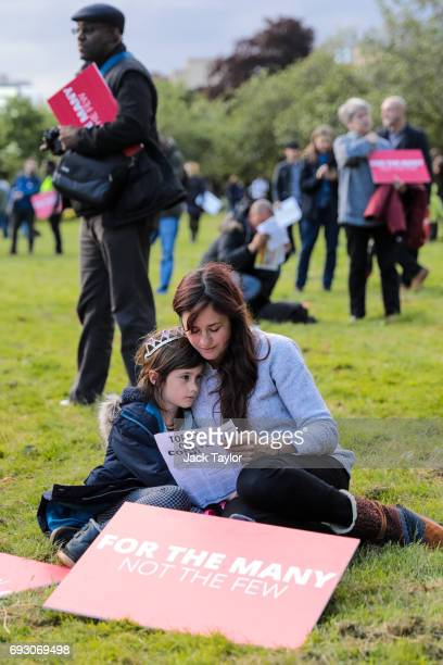 A woman and child sit next to placards ahead of a Labour Party rally in Park Hill park on June 6 2017 in Croydon England Labour Leader Jeremy Corbyn...