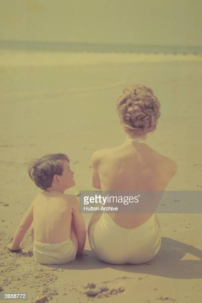 A woman and child sitting in the sun on a sandy beach