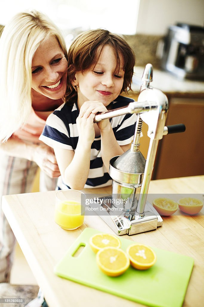 A woman and child squeezing oranges. : Stock Photo