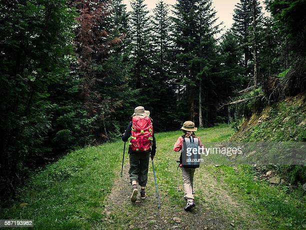 Woman and child trekking in the forest