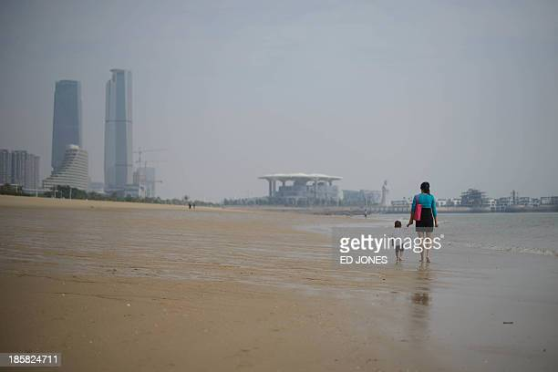 A woman and child walk on a beach in Xiamen Fujian province on October 25 2013 China's central bank has unveiled a new regime to allow banks to set a...