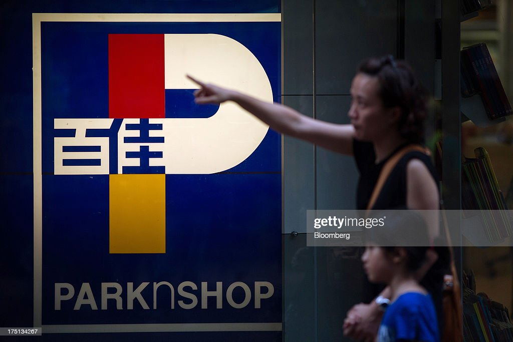 A woman and child walk past ParknShop signage displayed outside a ParknShop Superstore supermarket, operated by Hutchison Whampoa Ltd., in Hong Kong, China, on Thursday, Aug. 1, 2013. KKR & Co., the private-equity firm run by Henry Kravis and George Roberts, is evaluating a bid for Hong Kong supermarket chain ParknShop, according to two people with knowledge of the matter. Hutchison is seeking $3 billion to $4 billion for the chain and has asked potential buyers to submit bids by Aug. 16, people with knowledge of the process have said. Photographer: Lam Yik Fei/Bloomberg via Getty Images