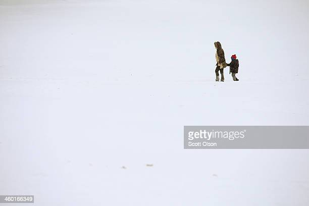 A woman and child walk through a snowcovered field in Humboldt Park on January 2 2014 in Chicago Illinois The Chicago area has been getting snowed on...
