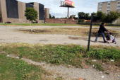 A woman and child walk through an empty lot September 30 2009 in Bridgeport Connecticut According to statistics from the US Census Bureau Connecticut...