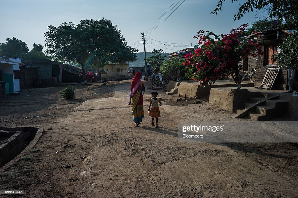 A woman and child walk through Nayakhera village, Maharashtra, India, on Thursday, Nov. 15, 2012. The Indian economy will expand 4.9 percent in 2012, the least in a decade, according to the International Monetary Fund. Photographer: Sanjit Das/Bloomberg via Getty Images