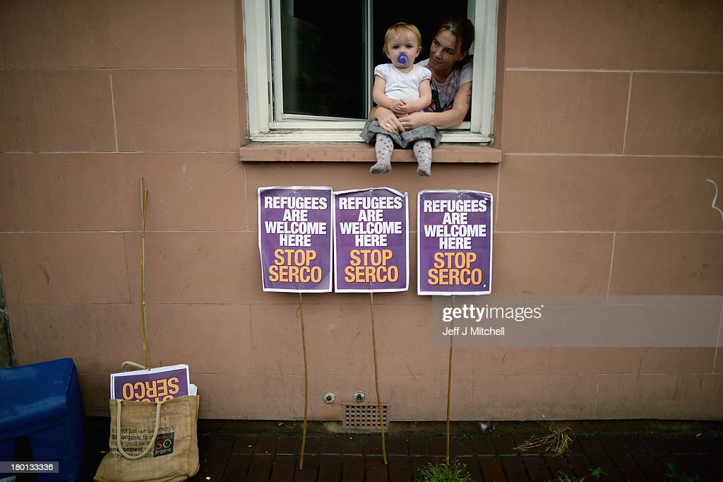 A woman and child watch from the window of their home as protestors gather outside the UK Border Agency to demonstrate against the home office Go Home campaign on September 9, 2013 in Glasgow, Scotland. The poster campaign began on the 29th of July and advises people not eligible to stay in the UK that they can be given assistance to go home. Charity groups have condemned the campaign as racist.