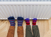 Woman and child wearing colorful pair of socks warming cold feet in front of heating radiator. Gas heater at home. Selective focus.