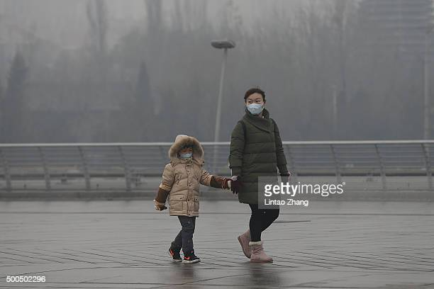 A woman and child wearing face masks on a day of heavy pollution on December 8 2015 in Beijing China Schools across Beijing have closed and outdoor...