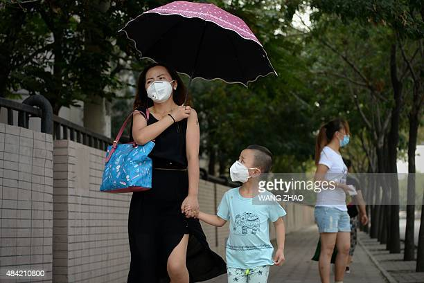 A woman and child wearing face masks walk along a road at the edge of the blocked off zone in Tianjin on August 16 2015 near the site of the...