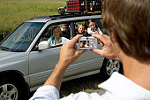 Woman and children (6-8 years) in car being photographed by man, rear view, in foreground