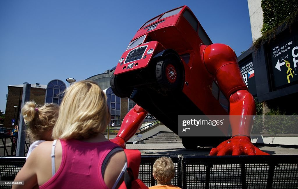 A woman and children look on July 26, 2012 at David Cerny's double-decker bus art installation 'London Booster'. The Czech artist has adapted a 1957 London bus and added huge mechanical arms which enable it to do press-ups. The work was commissioned by the Czech Olympic Committee, at Czech House.