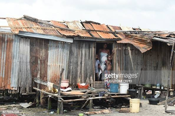 A woman and children stand at their makeshift home partly demolished by the authorities at Otodo Gbame waterfront fishing communities in Lagos on...