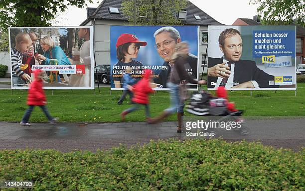 A woman and children walk past state election campaign posters for Social Democrat Hannelore Kraft Christian Democrat Norbert Roettgen and Free...