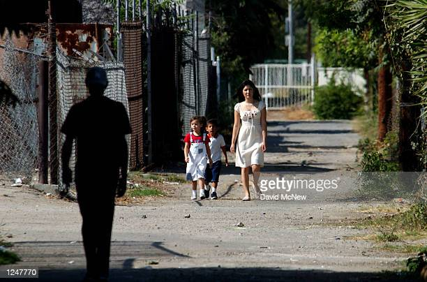 A woman and children walk toward a silhouetted figure in an alley where a new motionsensor camera is mounted on a power pole to keep watch over...