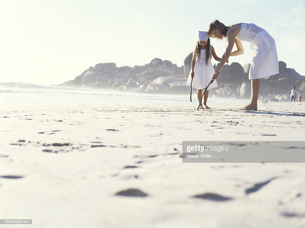 Woman and daughter (5-7) drawing in sand with sticks, ground view : Stock Photo
