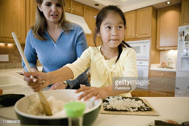 Woman and daughter in the kitchen making sushi