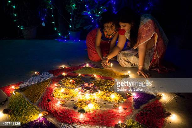 A woman and daughter lit earthen lamps on Diwali Diwali also known as Deepavali and the 'festival of lights' is a Hindu religious festival celebrated...