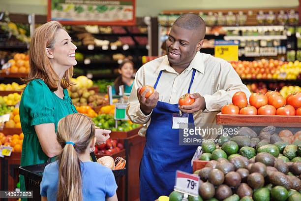 Woman and daughter talking about vegetables with produce worker