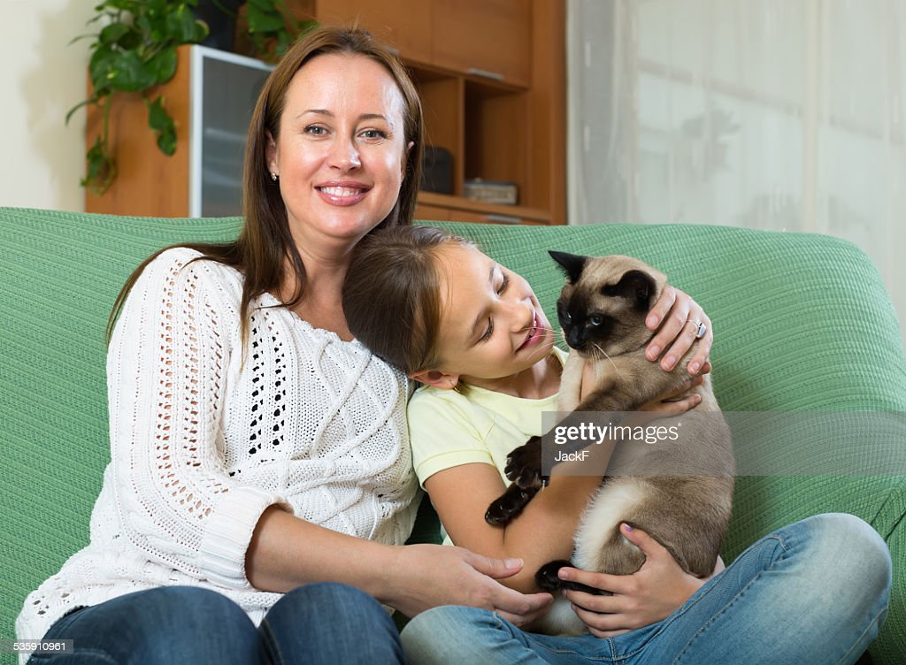 Woman and daughter with cat at home : Stock Photo