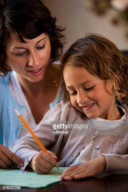 Woman and daughter writing