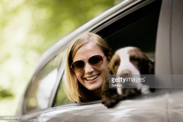Woman and dog in car window