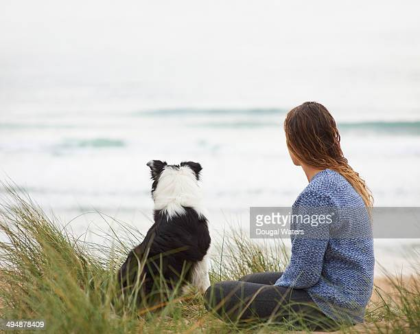 Woman and dog look out to sea.