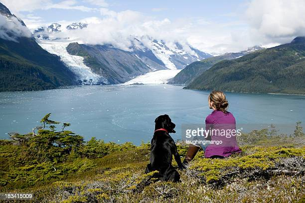 Woman and dog looking at landscape in Alaska