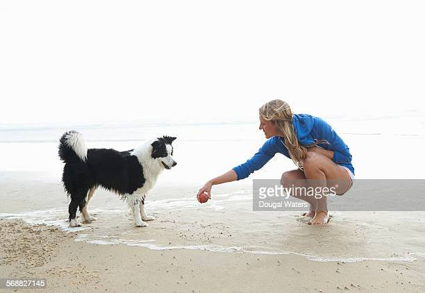 Woman and dog playing on beach.