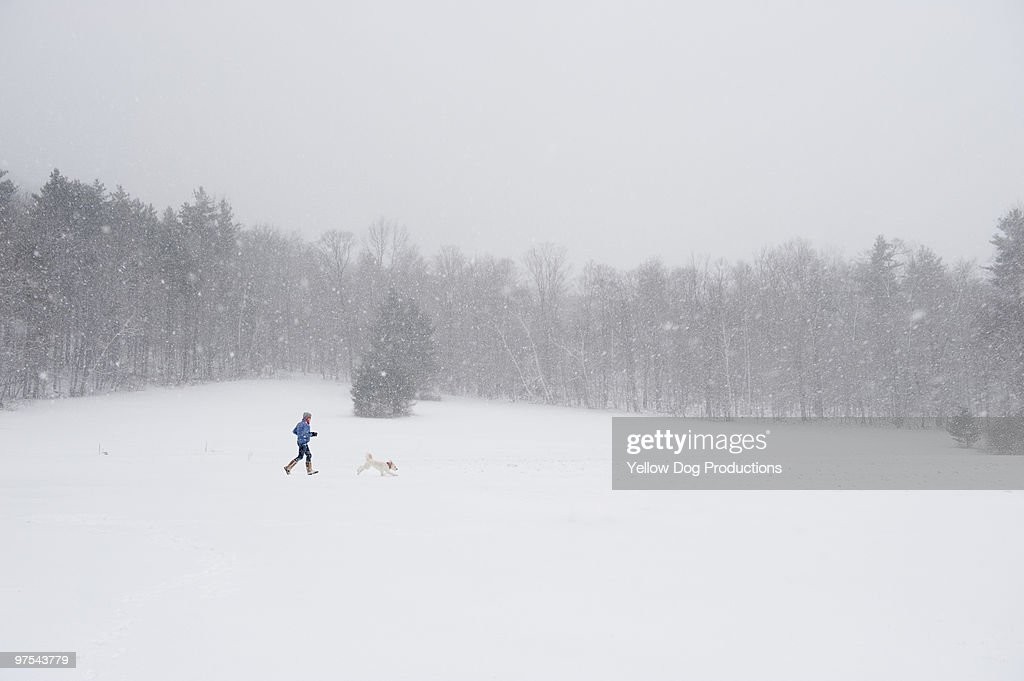 Woman and dog running during a snow storm