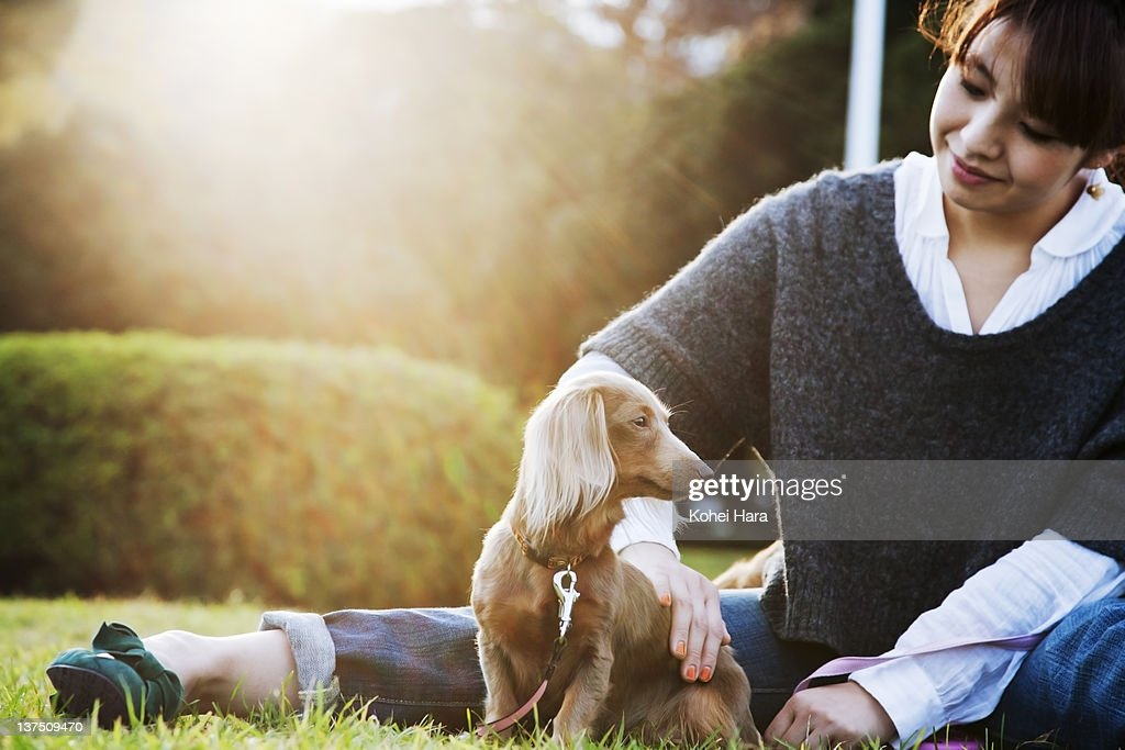 woman and dog sitting in the park : Stock Photo