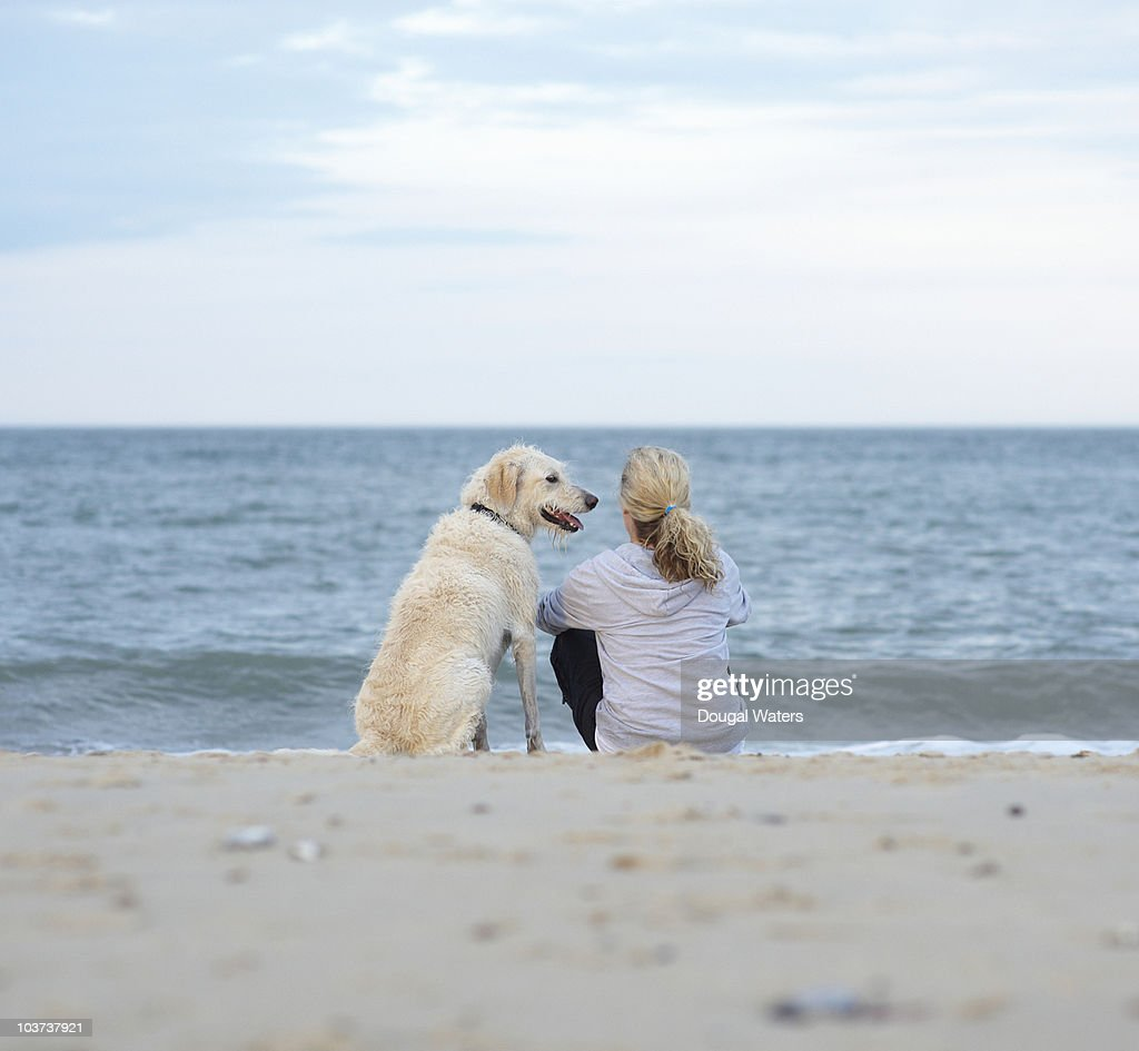 Woman and dog sitting together at beach. : Foto de stock