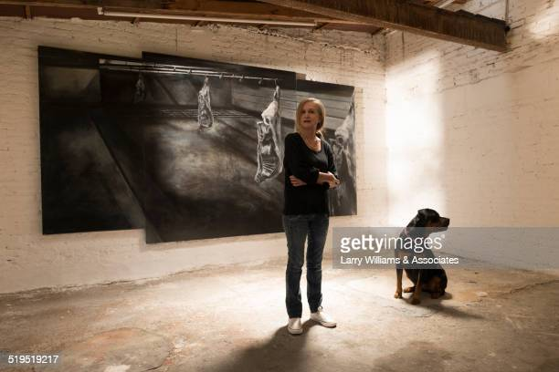 Woman and dog standing in art gallery