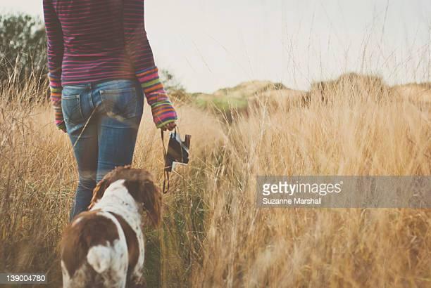Woman and dog walking through grass
