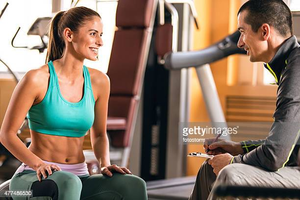Woman and fitness instructor talking in gym