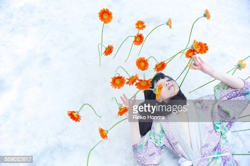 Woman and flowers bloom on top of the snow : Stock Photo