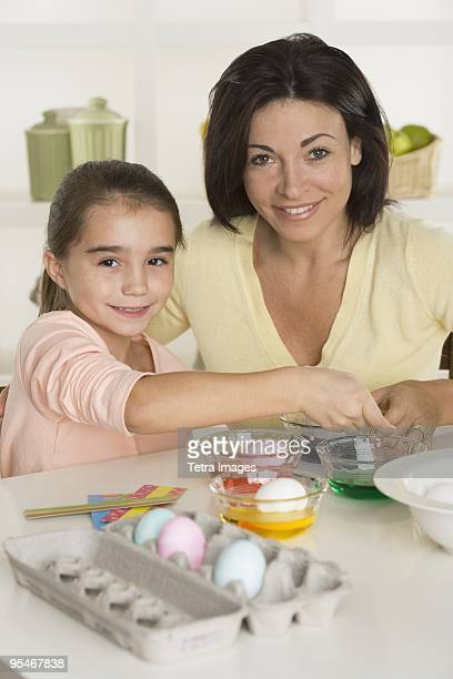 Woman and girl dying eggs