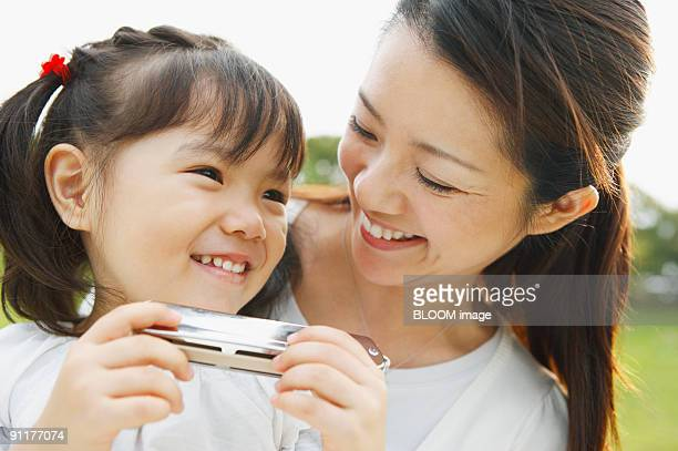 Woman and girl holding harmonica, smiling