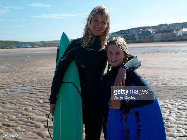 'Woman and girl (8-10) in wetsuits, holding surf boards on beach'