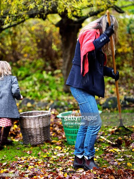 Woman and girl raking leaves