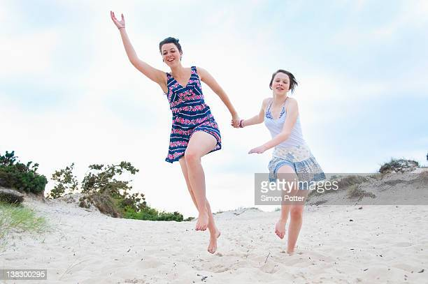 Woman and girl running on beach