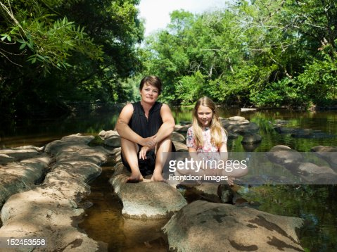 woman and girl sitting by the river : Stock Photo