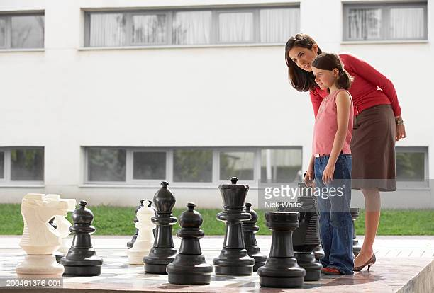 Woman and girl (8-10) standing by giant chess set