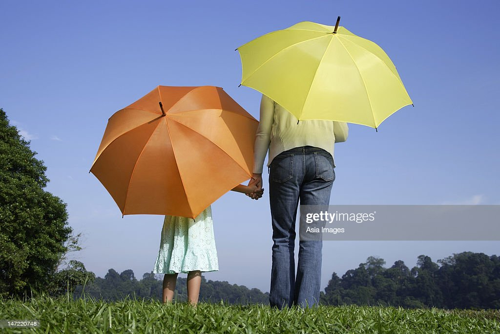 woman and girl standing in front of yellow and orange umbrellas : Stock Photo