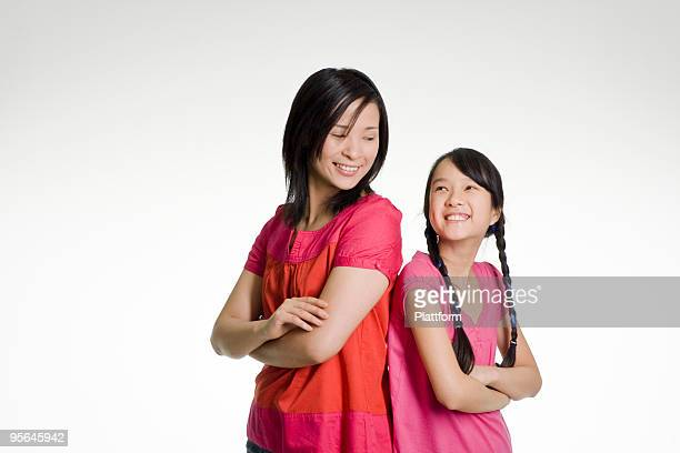 Woman and girl standing side by side.