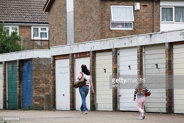 A woman and girl walk past car garages on a housing estate near the High Street in Stratford east London on August 15 2012Stratford welcomed the...